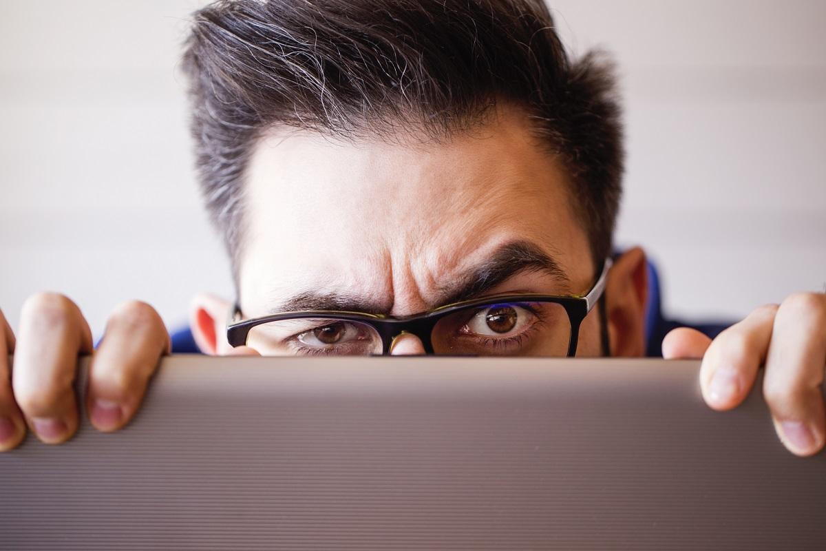 Mann schaut misstrauisch über silbernen Laptop