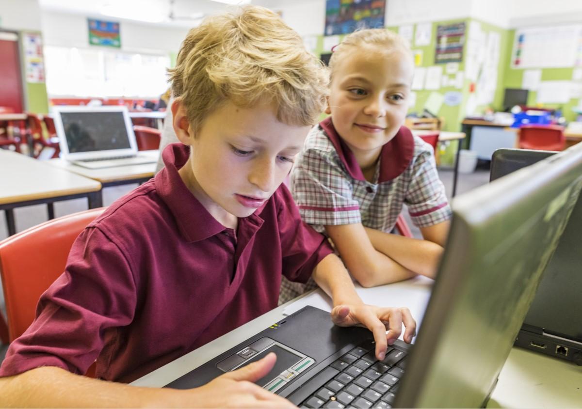 Schulkinder arbeiten mit Laptops