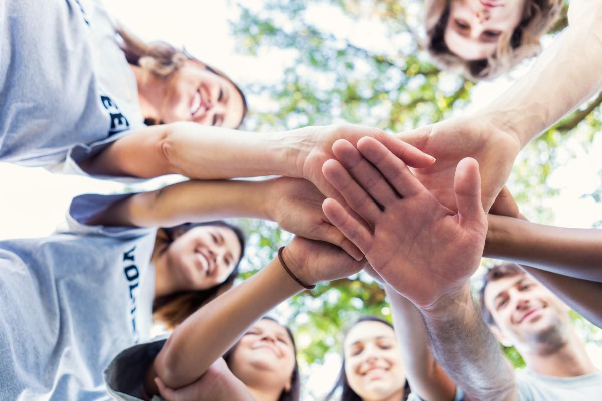 Gruppe von Mitarbeitern schlägt motiviert ein.