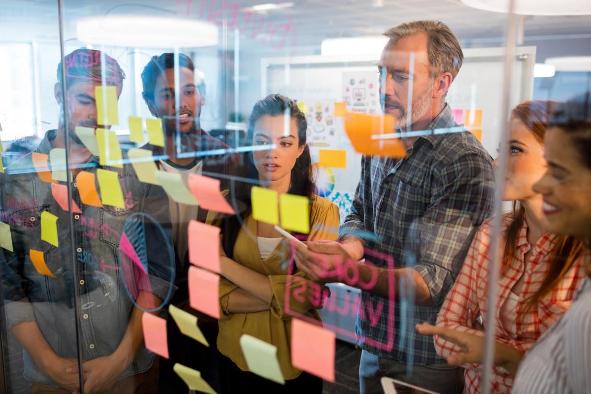 Programmierer besprechen sich vor einer Glaswand mit modularisierten Aufgaben auf Klebezetteln.