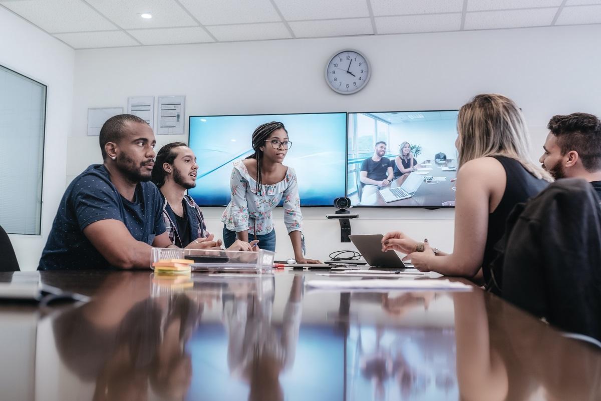 Fünf junge Unternehmer in einem Konferenzraum mit Videozuschaltung